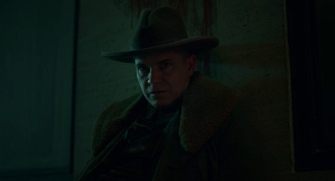 A closeup of Deafy's face looking directly into the camera as his body leans against a wall with a streak of blood running down the wall.