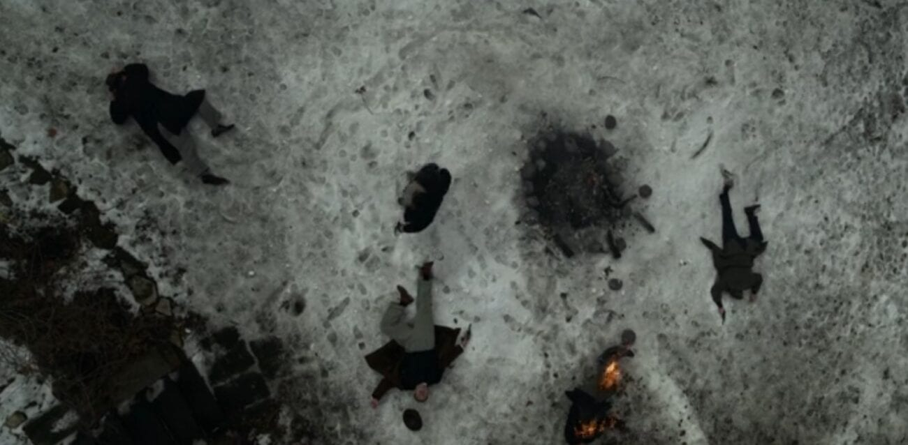 An overhead view of Gaetano standing among four dead bodies in the snow, one of them on fire.