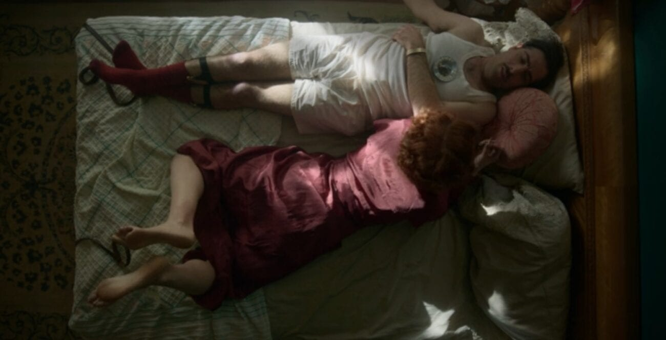Josto in bed wearing white shorts and tank top with maroon socks, while Oreatta lies beside him wearing a maroon robe. There is an ashtray on Josto's chest and leather straps at their feet.