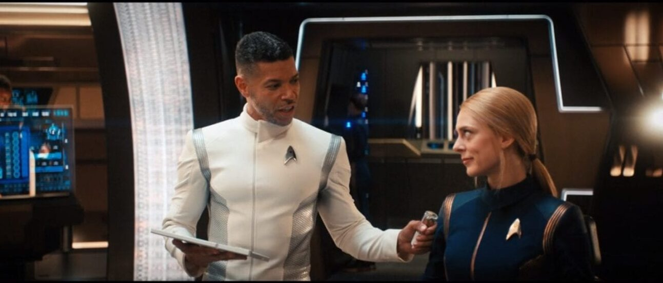 Dr Culber (Wilson Cruz) stands beside Lt. Nilsson (Sara Mitich) with his hand on her shoulder a padd in his other hand and medical equipment on the walls