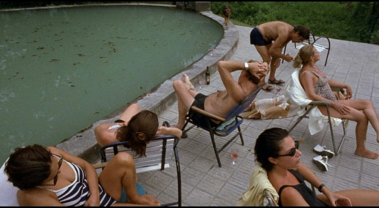 A group of adults sits by an unclean swimming pool with some facing towards the water, while other adults sit to their backs looking in the opposite direction.