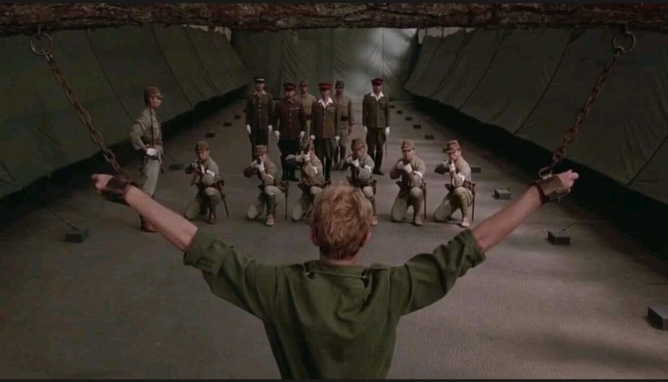 A wise shot behind Major Celliers (David Bowie) as his arms are raised by chains while a Japanese firing squad aims towards him
