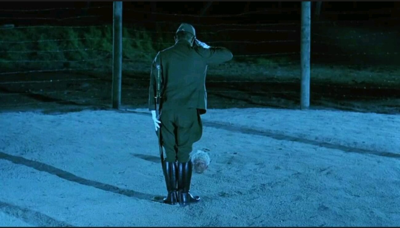 A long shot of Captain Yanoi (Ryuichi Sakamoto) as he stands and bows in front of the head of Major Celliers (David Bowie) as his body is buried underneath the sand