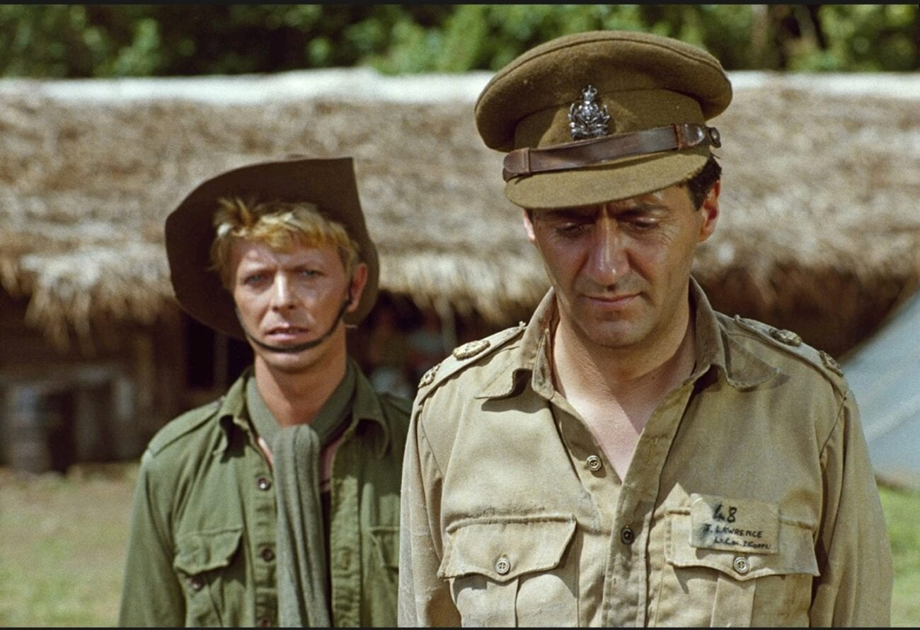 A medium shot of Colonel Lawrence (Tom Conti) looking down while Major Celliers (David Bowie) stands behind him and looks towards the camera