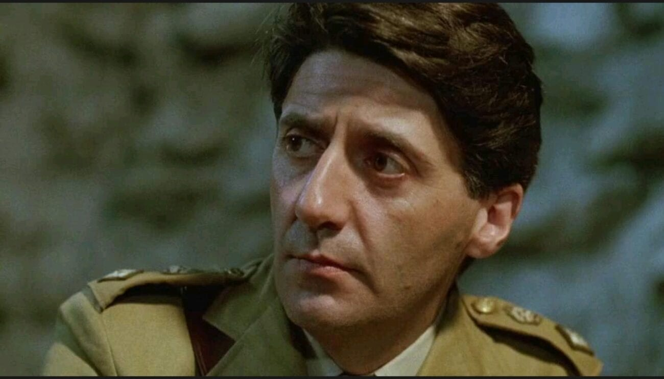 A medium shot of Colonel Lawrence (Tom Conti) looking towards the left of the camera frame.