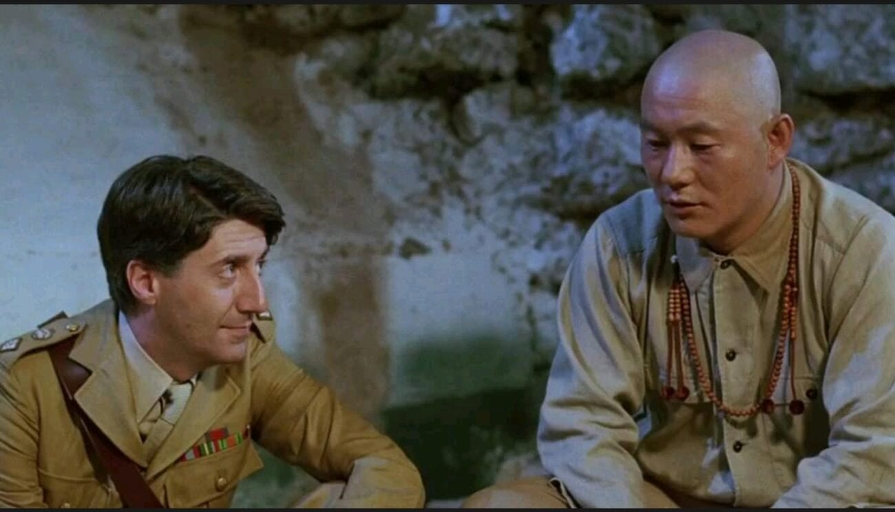 A medium shot of Colonel Lawrence (Tom Conti) sitting down beside Seargent Hara (Takeshi Kitano) while looking at him.