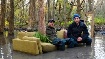 Justin Benson and Aaron Moorhead sit on a sofa in a swamp on the set of Syncronic