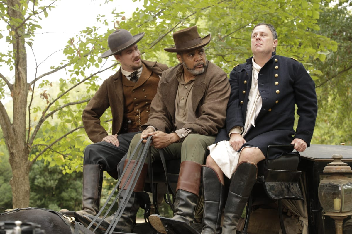 Cook (Rafael Casal) and the Coachman (Victor Williams) look at a distressed Colonel Washington (Brooks Ashmanskas) while sitting atop a carriage being driven through a wooded area