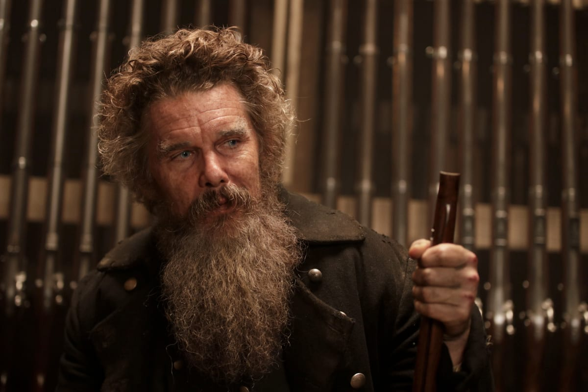John Brown (Ethan Hawke) stands looking toward the camera, his holding a rifle by the handle like a cane, behind him are many rifles lining the wall