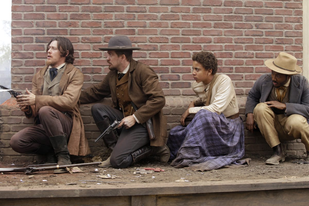 John Brown Jr. (Nick Eversman), John Cook (Rafael Casel), Onion (Joshua Caleb Johnson) and Bob (Hubert Pont-Du Jour) kneel in front of a brick wall, John Jr and Cook are holding guns