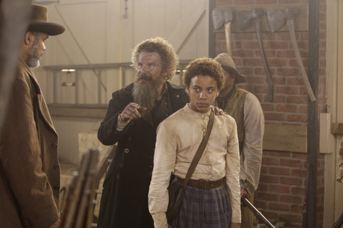 The Coachman (Victor Williams) looks on from the left of the shot as John Brown (Ethan Hawke) puts his arm on Onion's (Joshua Caleb Johnson) shoulder inside the armory with a banister, a man wearing a hat, and an axe on a brick wall behind them