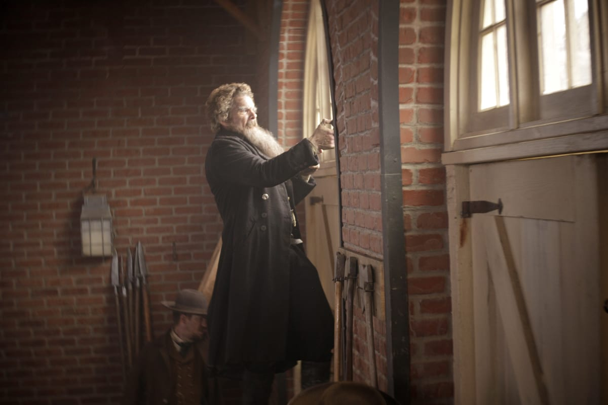 John Brown (Ethan Hawke) stands in an arched window in front a brick wall firing his two handguns