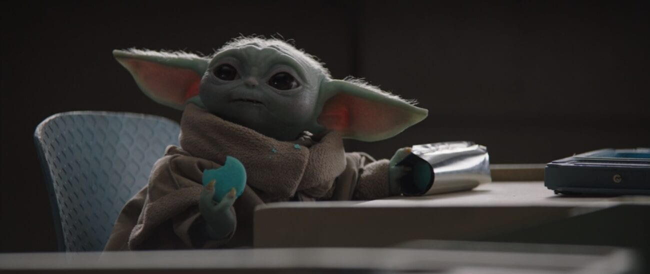 The Child (Baby Yoda) sits at a school desk eating a cookie he stole