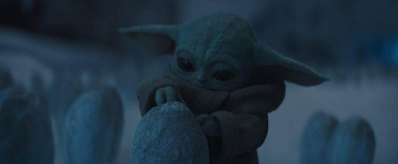 The Child (Baby Yoda) opens a spider egg to eat