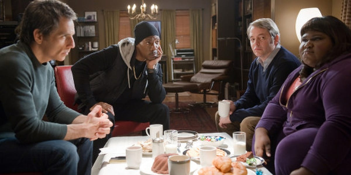 Ben Stiller, Eddie Murphy, Matthew Broderick, and Gabourey Sidibe sitting around a table in an apartment as their characters in Tower Heist