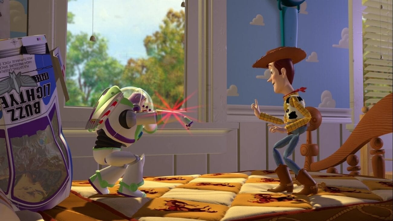 Buzz and Woody meet on Andy's bed, with Buzz (left) aiming his laser at Woody (right), who is attempting to calm Buzz down. Buzz's spaceship packaging lies crumpled behind him.