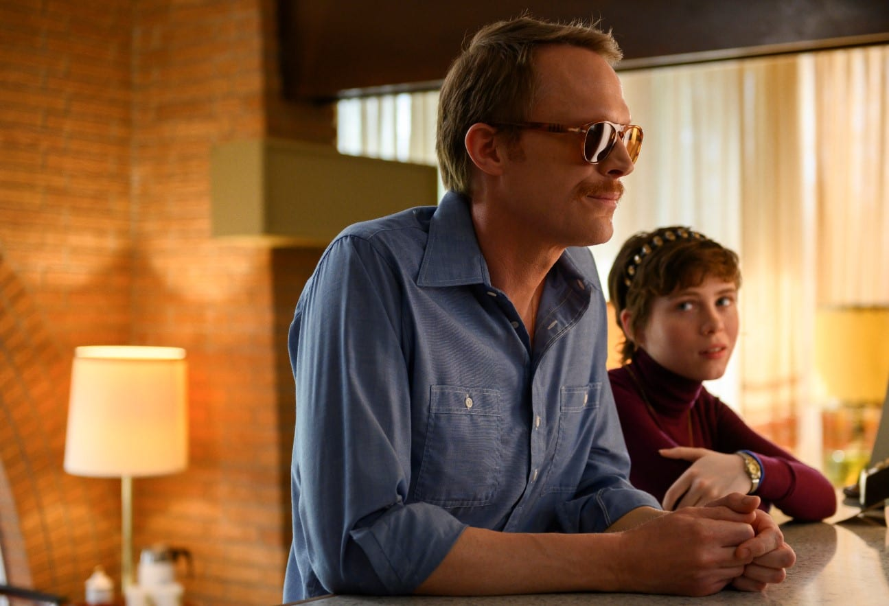 Frank leans over a motel check-in desk wearing sunglasses and folding his hands, Beth stands beside him looking at him