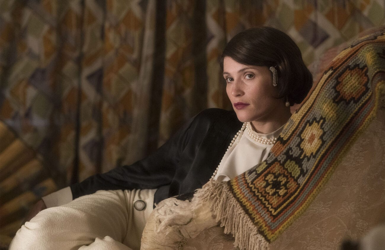 Gemma Arterton as Vita is wearing stylish clothing, including trousers, and is lounging on a seat