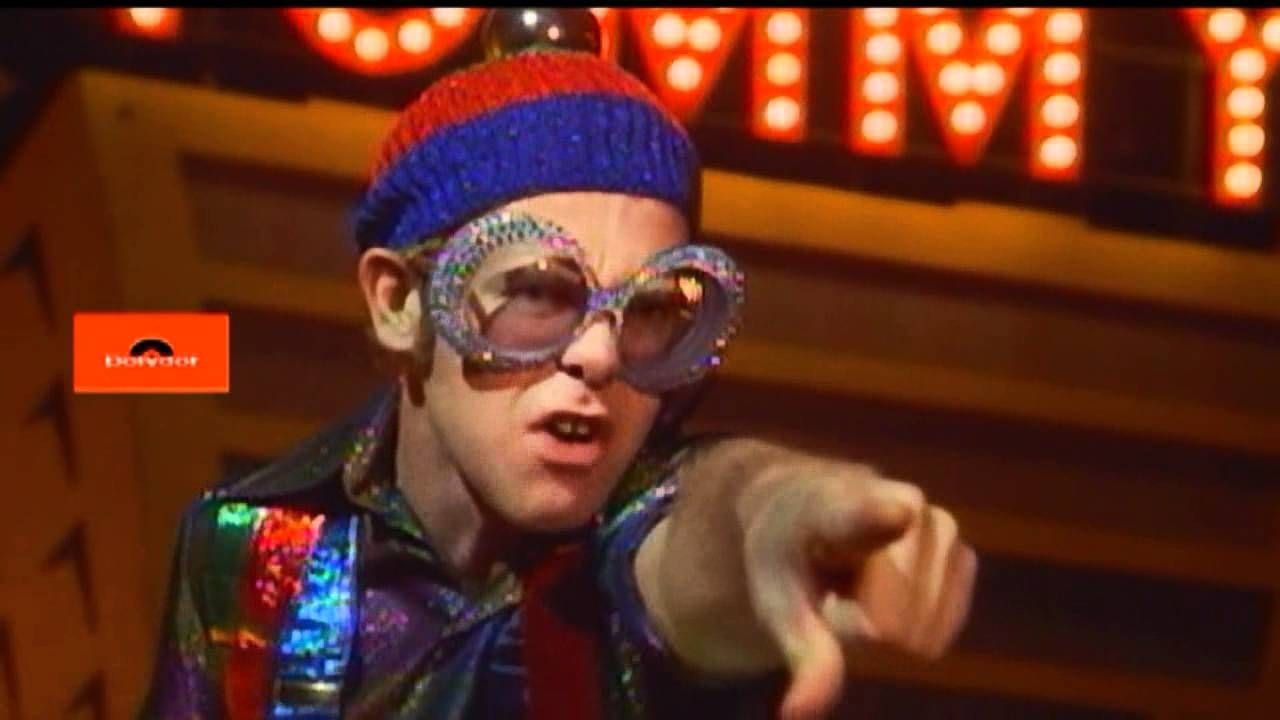 Elton John as the Pinball Champ, pointing at Tommy
