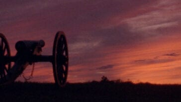 A canon in shadow on the left of the frame with a vivid red, orange, and purple sunset on the horizon