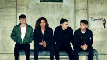 the clockworks band sitting at a railway station