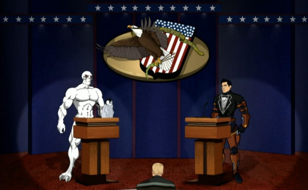 The mutant Killface and Xander Crews on a debate stage in front of podiums. Crews is wearing a tuxedo shirt and Killface has a penguin on his podium.