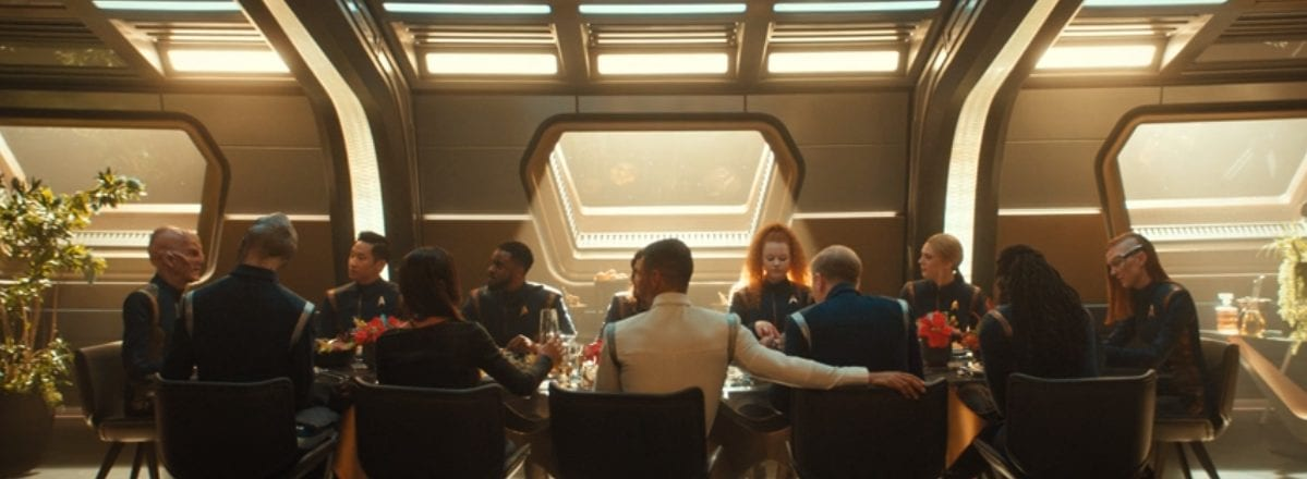 The Discovery bridge crew sits around a table filled with food in a room brightly lit from a square window and skylights