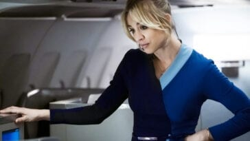 Kaley Cuoco looks down towards a passenger as she stands in the aisle of a plane in The Flight Attendant on HBO Max