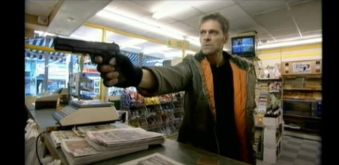 Mark Heap holds a man up in a shop with a gun, demanding his change in episode 2