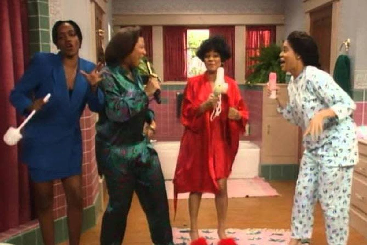 The women of Living Single sing into hairbrushes in their bathroom