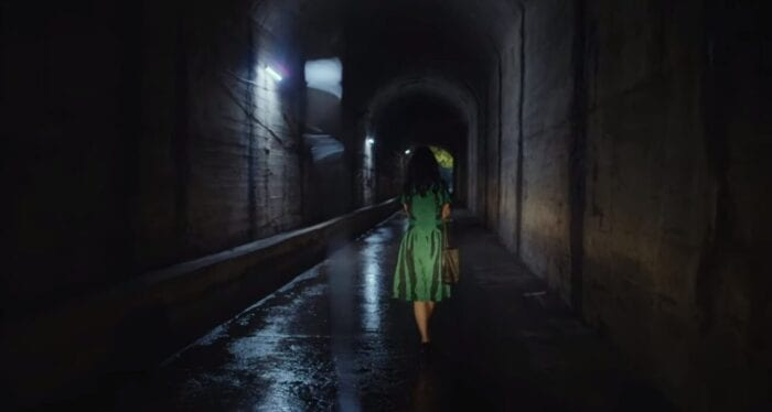 A woman in a bright green dress walks away down a long tunnel with the headlights of a car on her