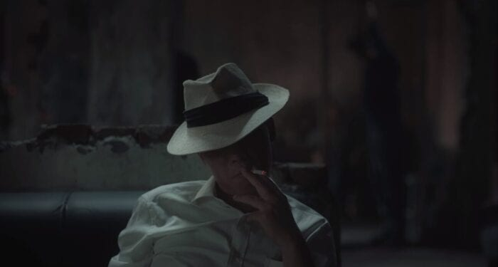 Zuo sits on the end of a couch in a fedora, smokes a cigarette. His first and second finger surround the butt as his cheeks deflate from inhalation.