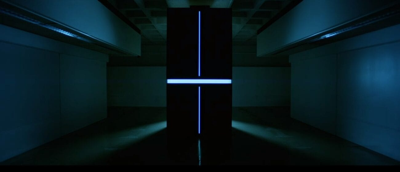 A supercomputer glows from a cross section of perpendicular lines in an otherwise empty room.