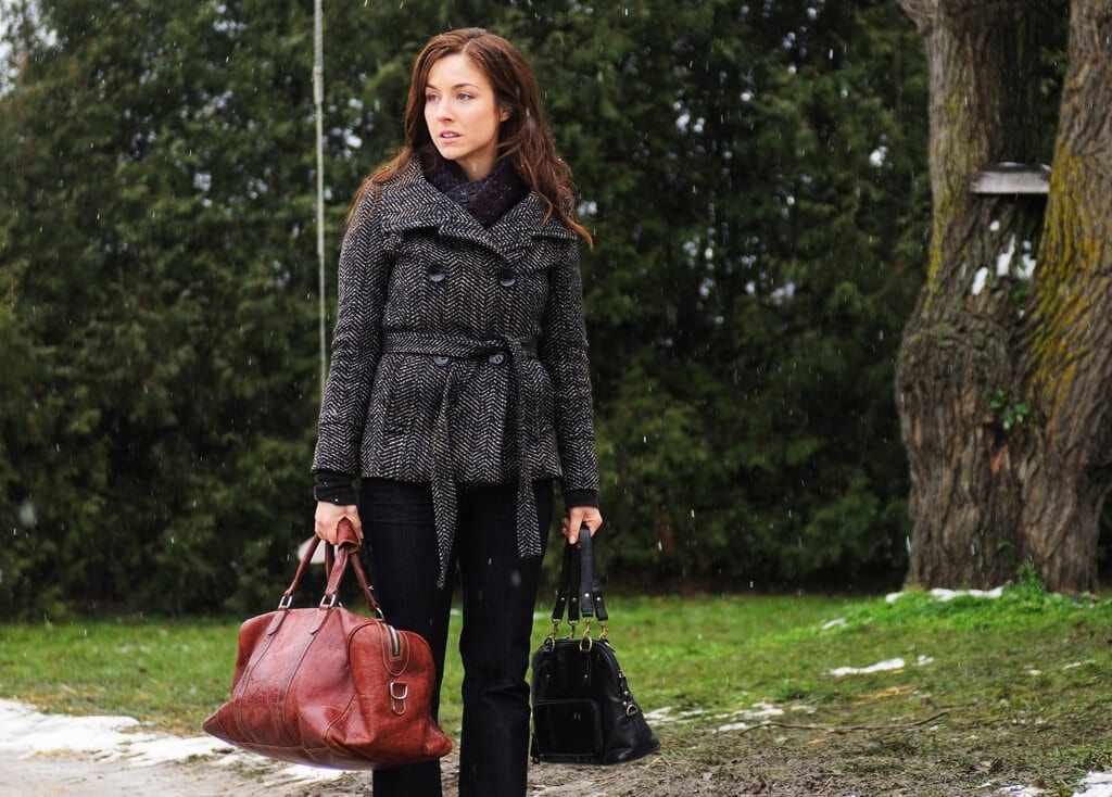 Erica looks offscreen while holding two bags and wearing business casual clothes.