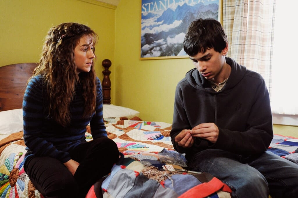 Erica and Leo sit on his bed while he rolls a joint.