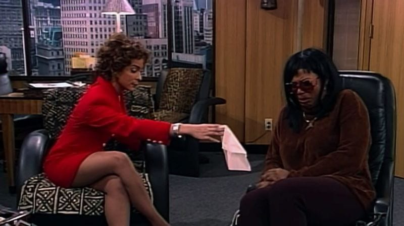 Khadijah at a therapist's office, in sunglasses and a wig. The therapist is handing her a tissue