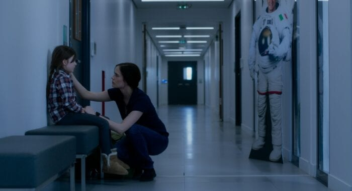 Sarah consoles her sitting daughter Stella in a hallway.