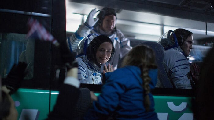 Sarah waves goodbye to her daughter from a bus before boarding her rocket.
