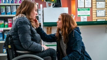 Diane squats down to comfort a wheelchair-bound Chloe in a pharmacy.