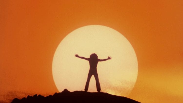 Silhouette of Tommy on a mountaintop, raising his arms against the sun
