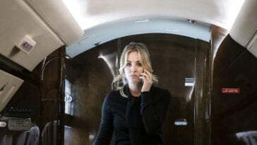 Cassie holds her phone to her ear as she boards a private plane.