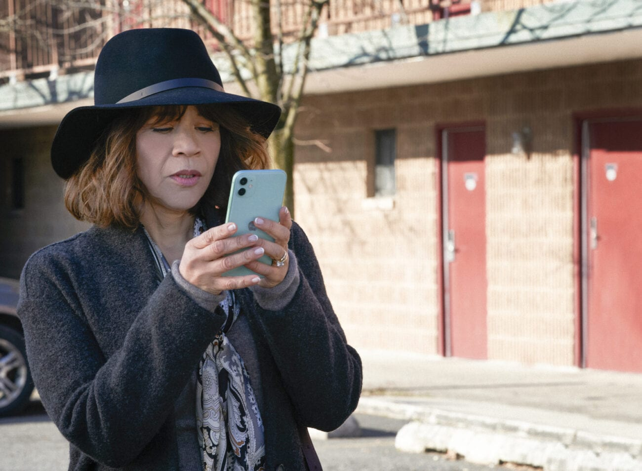 Megan texts on her phone while waiting at a motel.
