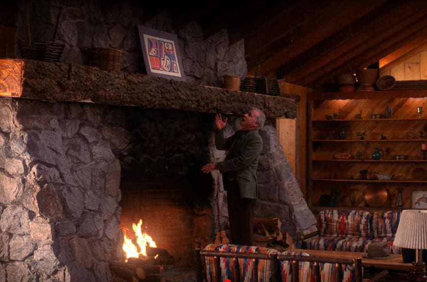 Pete stands by the fireplace in the Great Northern talking to the wall