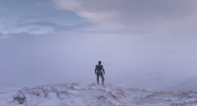 a lone man stands on a rocky peak looking over land covered in icy fog