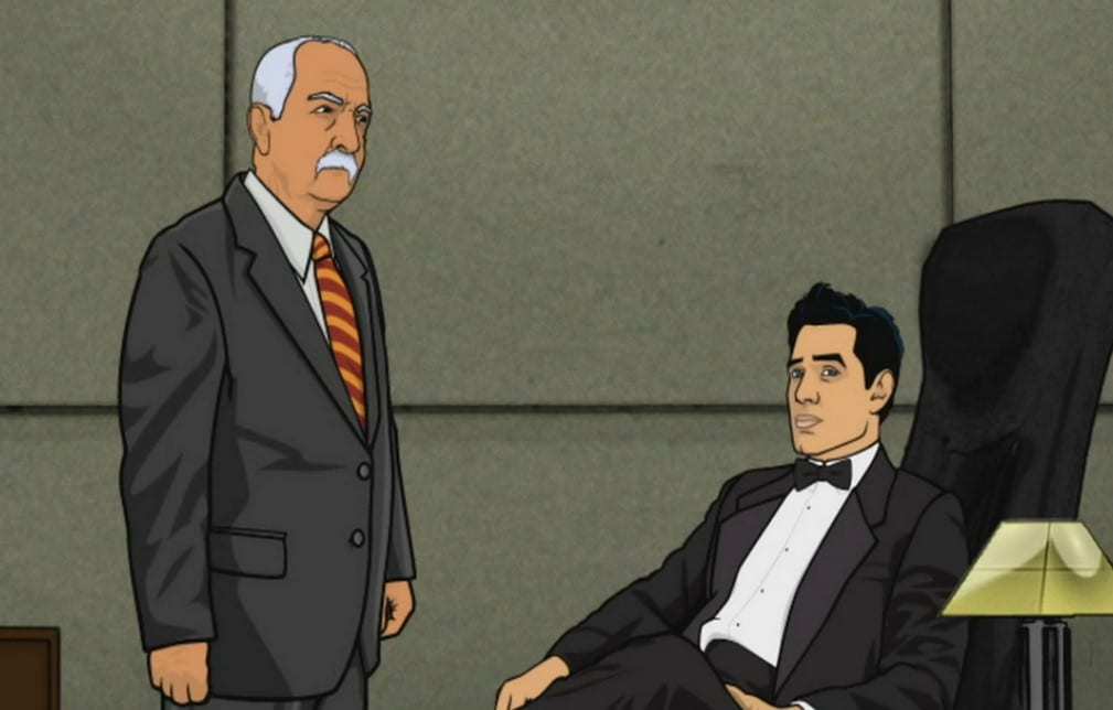 Xander Crews in a tux sitting at his desk, standing next to him is his business partner Stan.