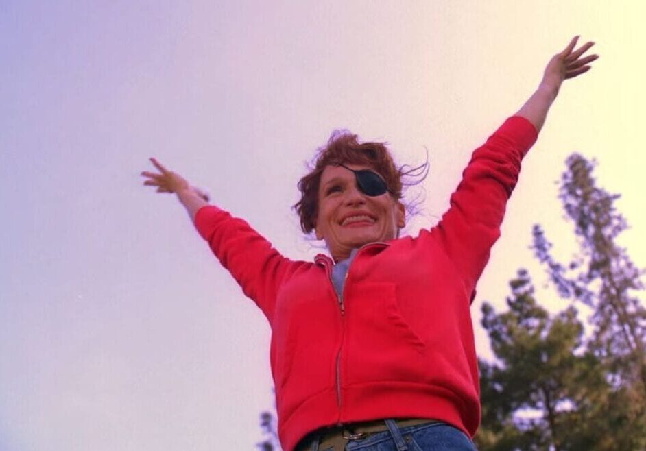 Nadine, as her cheerleader persona, stretches her arms skyward, smiling, a patch over her left eye