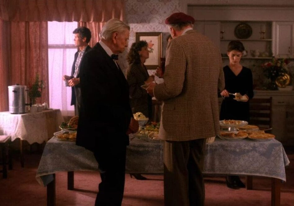 Two old men take food from a banquet table at a wedding reception.