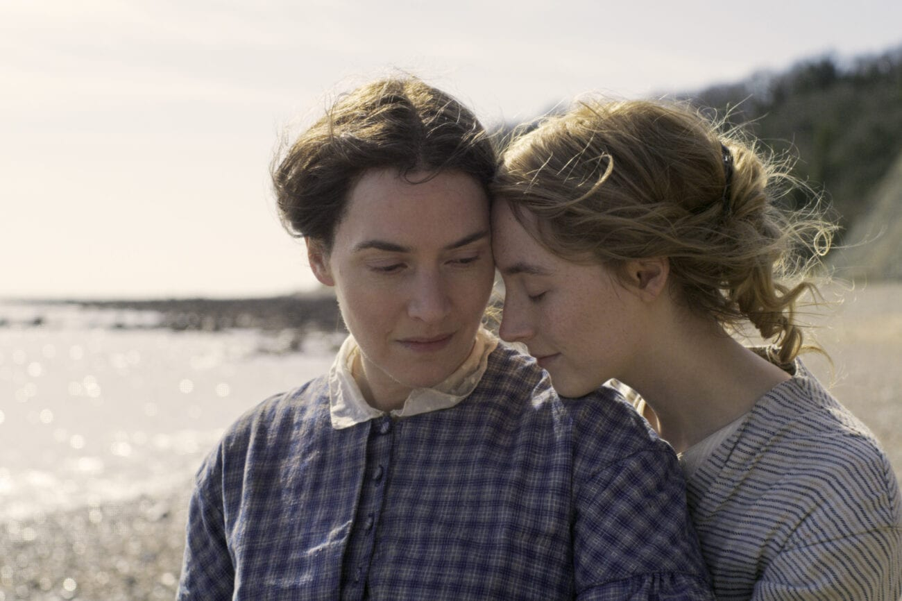 "Charlotte (Saoirse Ronan) snuggles up to Mary(Kate Winslet) on the Beach in a still from ""Ammonite"""