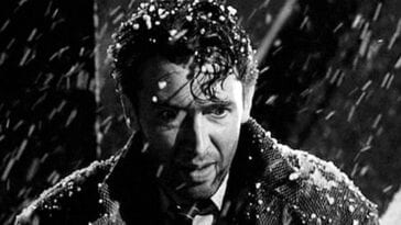 George looks forlorn as snow falls on him on the bridge