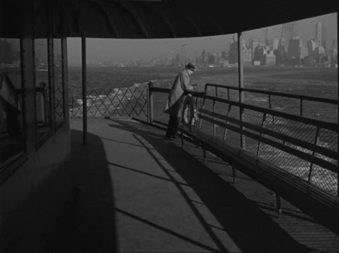 Still from Blast of Silence. Frankie Bono stands alone on the Staten Island Ferry. The New York City skyline looms in the distance.